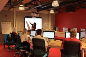 woman instructs a class in the computer lab