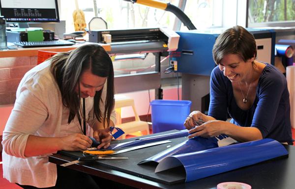 two women peeling vinyl stickers