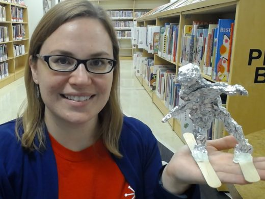 Person holding aluminum foil sculpture