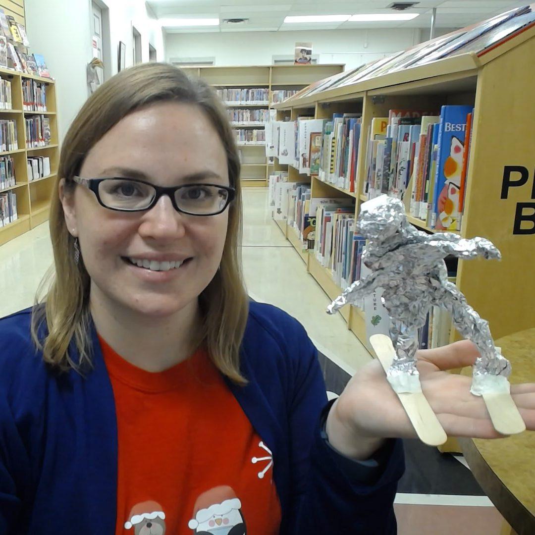 Person holding aluminum foil sculpture