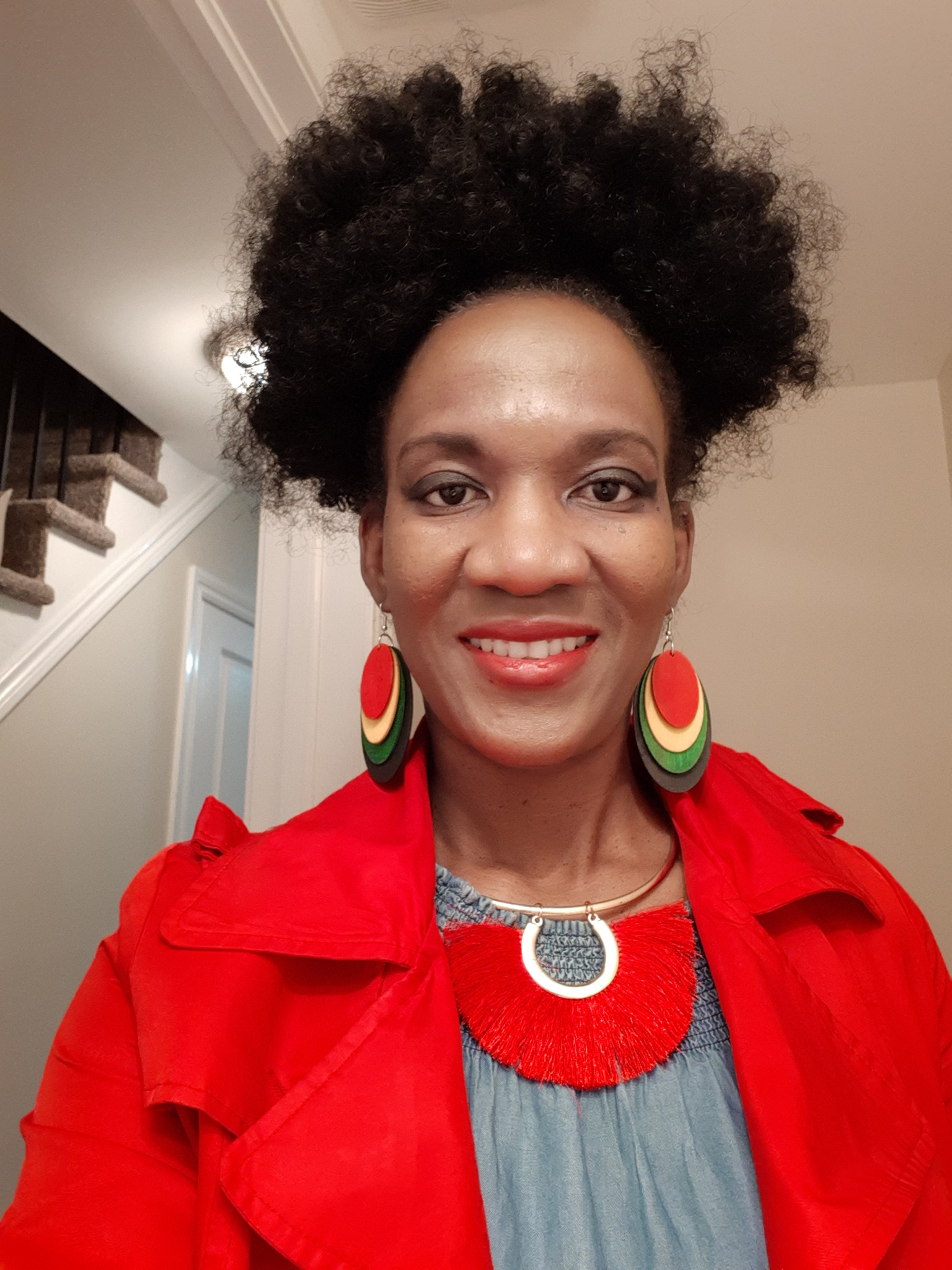 Smiling Black woman with curly hair and red jacket